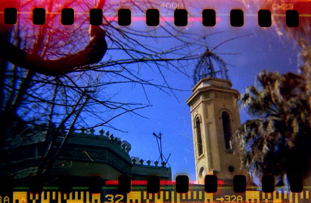 Home-scanned photo with sprocket holes of the tower of the Can Deu building in Les Corts quarter, Barcelona.