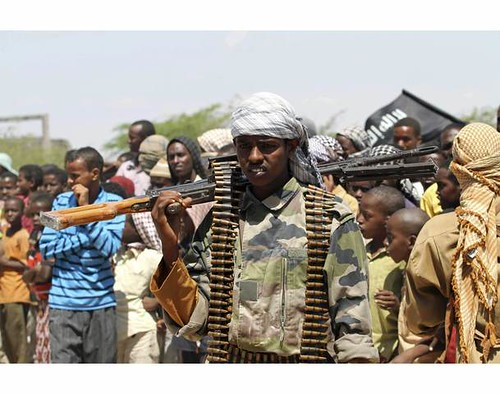 An Islamist al Shabaab soldier carries his gun at a meeting between al Shabaab and rebel group Hizbul Islam, in southern Mogadishu, January 1, 2011, where the two groups officially merged. by Pan-African News Wire File Photos