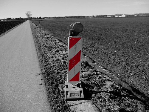 Warning - roadworks sign in black and white with red color cut out (partial de-saturation)