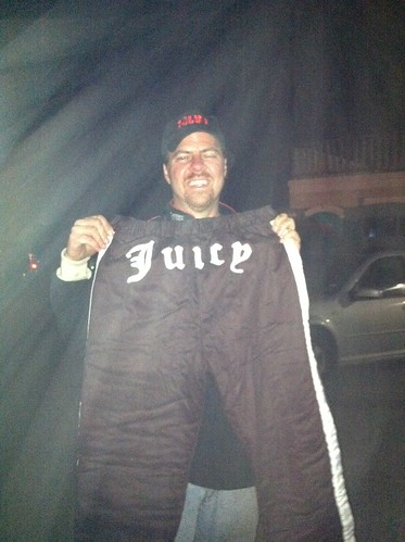 Brian holds his gift- racing pants with the word 'Juicy' stitched over the bottom