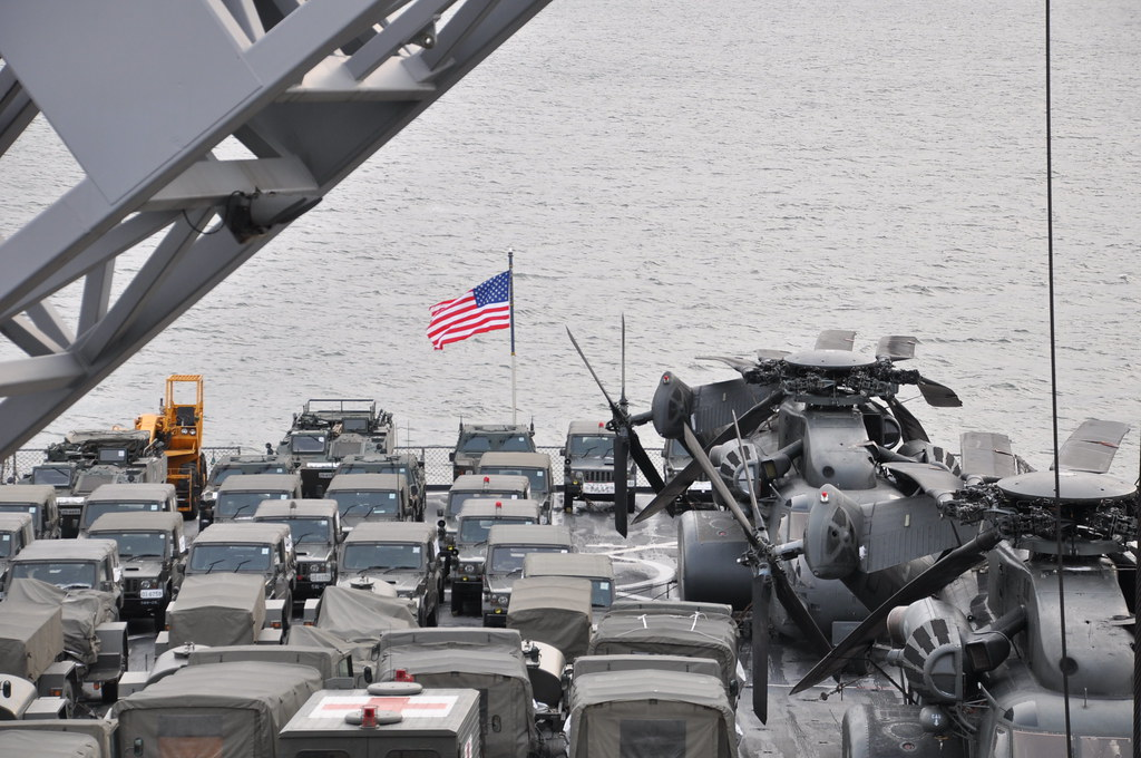 USS Tortuga's flight deck is filled with Japanese trucks enroute to area affected by tsunami.