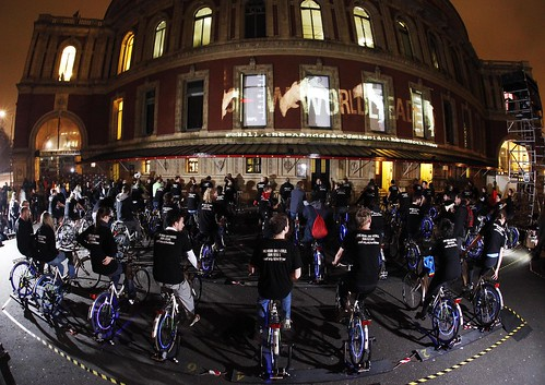 A team of 60 static cyclists use pedal power to create a light projection onto the Royal Albert Hall