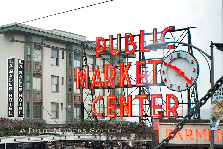 a close up rainy photo of the Pike Place Market in Seattle highlighting the bright red market sign and clock