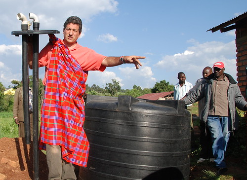T.H. Culhane demonstrating how to build a biogas generator, in his newly acquired Maasai shuka