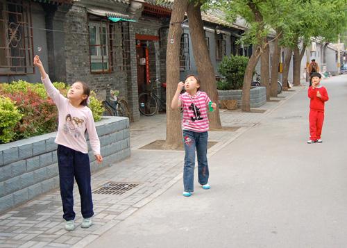 Two girls blowing soap bubbles on a sidewalk