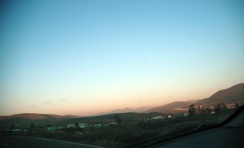 Driving into Mexico, just across the border, as the sun sets orange and blue, landscape, Mexico by Wonderlane