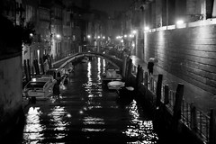 Fino A Domani, Venice (flatworldsedge) Tags: bridge venice bw italy white black blur rain night umbrella reflections boats canal noir alone candid grain bn lamps canon50mmf18 venezia oldage watercraft gaslig