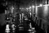 Fino A Domani, Venice (flatworldsedge) Tags: bridge venice bw italy white black blur rain night umbrella reflections boats canal noir alone candid grain bn lamps canon50mmf18 venezia oldage watercraft gaslight explored yahoo:yourpictures=waterv2