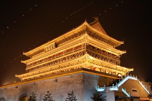 Nachaufnahme in Xi'an: Trommelturm vor Miniwinddrachen im Scheinwerferlicht