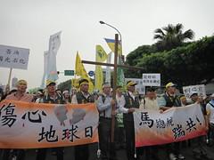 總統府前,民眾手持「傷心地球日、馬總統踹共」布條,要求國光石化撤案。