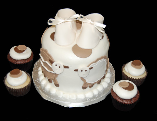 chocolate and cream colored polka dot cupcake tower with sheep and baby shoes