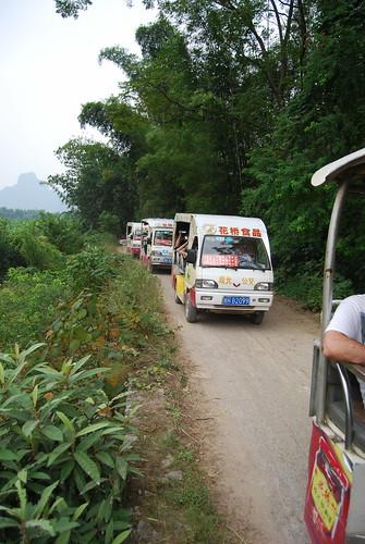 Entgegenkommender Konvoi von Rikschas, die Touristen aus Guillin in der Nähe von Yangshou über die Felder führen