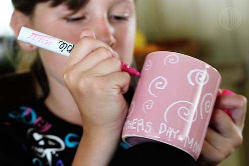 child coloring a cup