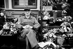 Potted Garden (Steve Gray) Tags: street old city flowers portrait plants man philadelphia window senior hat garden downtown sitting pennsylvania candid townhouse streetportrait courtyard jacket mature age philly aged relaxed seated repose gentleman potted gardener wrinkled couryard seniority stevengray
