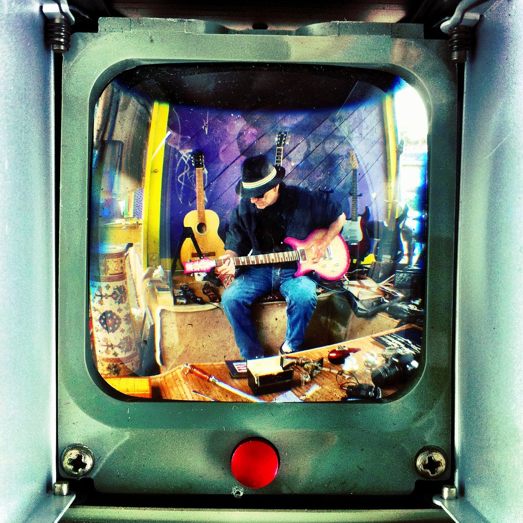 Shooting through the viewfinder of an old Anscoflex camera. I just bought it from the guy playing guitar.