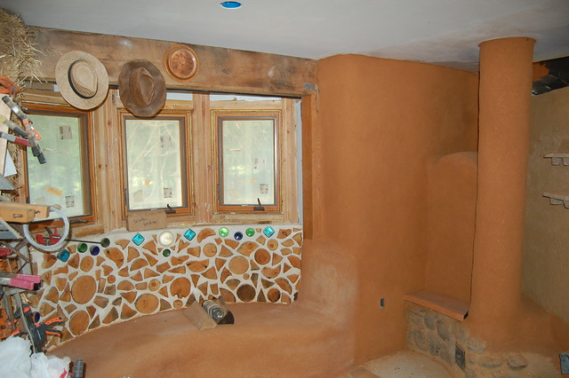 Above, The Dining Room Area With Cordwood, Cob Bench, The Dining Room Wall,  Plastered Stove Pipe, And Stone Work Around The Base Of The Masonry Stove.