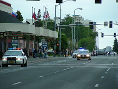 Police cars speed past the Transit Center