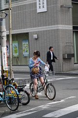 Woman texting on bike in Kyoto