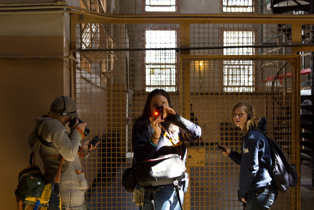 Reflexivity at its best! Sandwich concentrated on the audio tour, Daniella snapping Connor, and Kathleen posing for Connors shot, Penitentiary, Alcatraz Island.