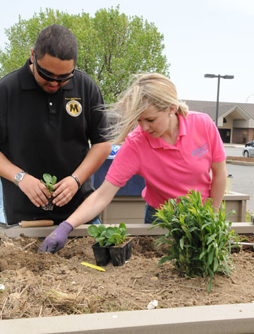 NRCS employee Clarissa Blackiston works with MANRRS student Ian Silva to plant Brussels sprouts in one of the raised beds of the People's Garden.