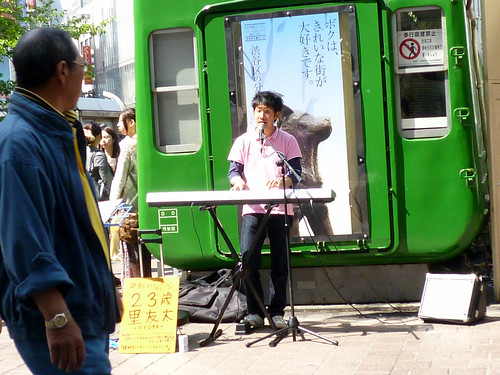 緑の電車前で歌ってる人