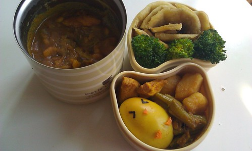 In een thermosbeker zie je surinaamse massala met aardappelen, kip en sperziebonen. De saus is ietwat bruin. Links bovenin zie je een kleiner doosje (sidecar) met een tot roos opgerolde roti en 3 broccolirozen. Daaronder zie je nog zo'n doosje met de inhoud van de curry los: sperziebonen, aardappelen en kip. Daarbij een kuikentje gemaakt van een kerrie-ei met een snavel en poten van wortel en ogen van nori-zeewier