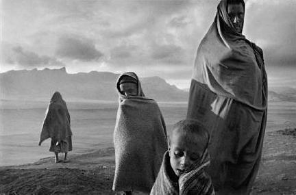 Envoltos em cobertores para se defender do vento frio matinal, refugiados esperam em frente do, campo de Korem. Etiopia, 1984