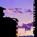 The purple evening sky seen between silhouetted buildings.