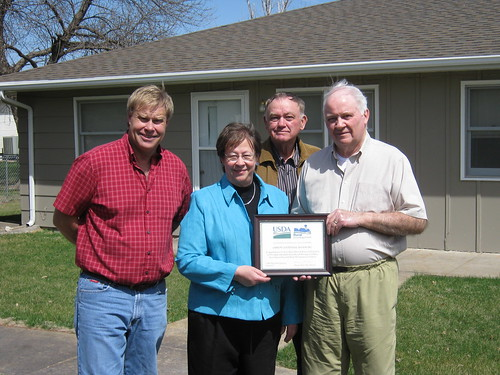USDA Rural Development Nebraska State Director Maxine Moul presented a plaque for the more than 40 years of service by Gibbon's Centennial Manor to board members, left to right, Bob Godberson, Duane Frazier and Duncan McGregor.  Board members not present for the April 2 event were Bob Clevenger and Fred Reed.