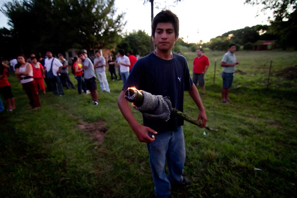 Un voluntario enciende una de las primeras antorchas, para luego, con ayuda de otras personas ir encendiendo las demás antorchas que iluminan el camino que recorrerá la Virgen. (Tetsu Espósito - San Ignacio, Paraguay)