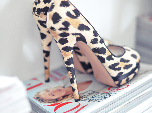 leopard heels on a stack of magazines