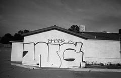 WG (QsySue) Tags: blackandwhite slr graffiti tag wideangle 35mmfilm ek canonae1program wg rialto closeddown expiredfilm inlandempire sanbernardinocounty developedathome 28mm128 35mmfilmcamera ehoe ehoer ilfordpanfp4125 ilfordpanfp4plus125