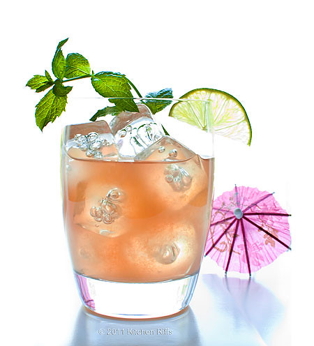 Mai Tai in glass with lime wedge and mint sprig garnish with cocktail umbrella