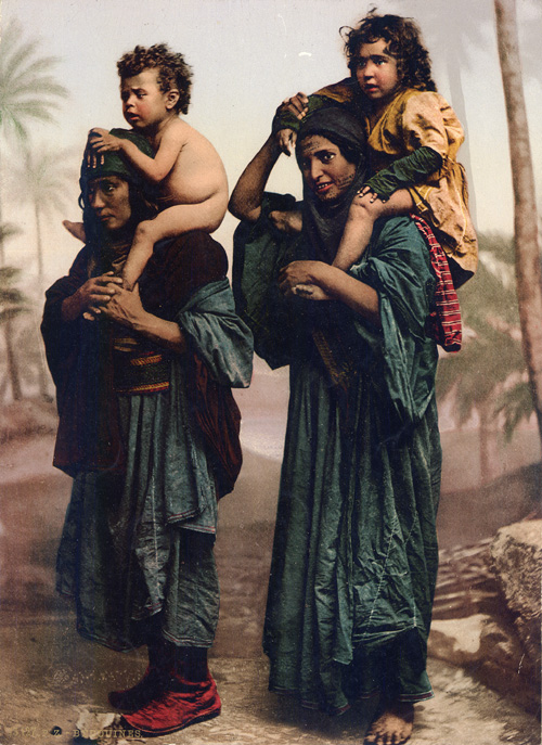 Studio portrait of two Bedouin women with children on their backs. Photochrome of original image attributed to Maison Bonfils. Penn Museum image #166009