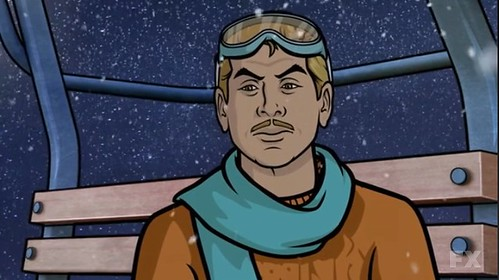 Ray Gilette, with blonde hair, a blonde trimmed mustache, black eyebrows, teal goggles, a matching teal scarf, and a burnt orange jumper, sitting on a ski lift. The shot frames his head and shoulders, and there is snow in the background. He looks resigned, tired, and pensive.