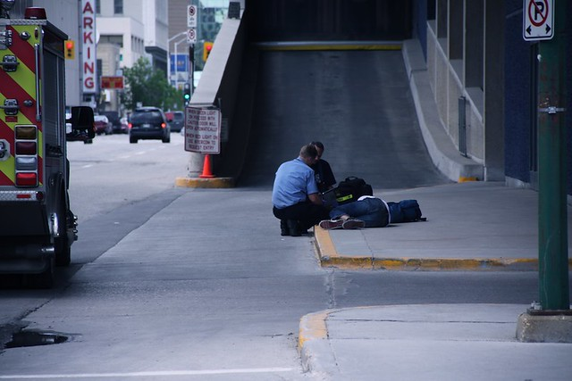 Walking near the Winnipeg Convention Centre, I spotted two EMS responders checking the vitals of someone who appears to have passed out on the street due to drugs or alcohol.