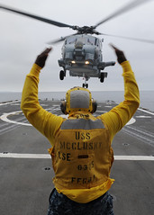USS McClusky Sailor guides an SH-60R Sea Hawk helicopter on the flight deck (Official U.S. Navy Imagery) Tags: navy helicopter pacificocean sailor usnavy guidedmissilefrigate enlistedlandingsignalman landingqualifications ussmccluskyffg41 boatswainsmate sh60rseahawk