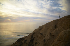 Woman running on ridge at sunset with Pacific Ocean in the background. Torrey Pines, Southern California. (stanevansphoto) Tags: ocean california travel sunset sea summer vacation sky people cliff woman plants beach nature water silhouette sport clouds fun outdoors happy person coast athletic sand paradise surf play outdoor background young lifestyle wave happiness running run surfing palm adventure surfboard tropical leisure recreation activity splash runner carefree released active surfboarding sportsactivity