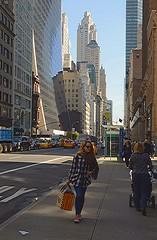 Color of Autumn 2016 In NYC (Candid of Shopper On 57th St. NYC With Architecture In View) (nrhodesphotos(the_eye_of_the_moment)) Tags: thumbdsc3830102472 theeyeofthemoment21gmailcom wwwflickrcomphotostheeyeofthemoment 57thstreet shopper streetscene skyscrapers women cars autos colorofautumn2016innyc manhattan nyc people refelctions shadows outdoor street scene perspective busstop display kiosk flag road city architecture streetlights pedestrians
