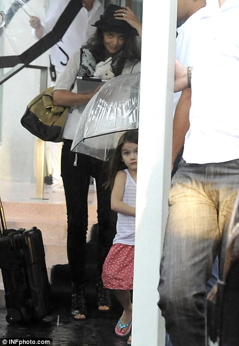 Rain dance! Smiling Suri Cruise larks around in miserable Miami  3