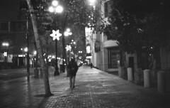 Midnight wanderer (m_travels) Tags: man stranger street depthoffield bokeh dark urban city 35mmfilm analogue blackandwhite filmphotography selfdeveloped analog argentique d76 chemicals homeprocessing developing kodaktrix400 market sf sanfrancisco night mood dreamy christmaslights kodakd76