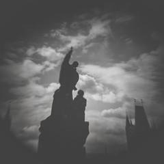 Tempus fugit: Praga (miemo) Tags: charlesbridge czechrepublic holga prague praha analog analogue bw blackandwhite clouds europe film kodak silhouette sky statue teleconverter tmax400 vignetting