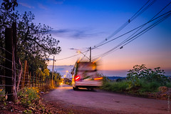 Bus passing by - M9080183.jpg (caiopetronio) Tags: olympus omdem1 lumixg20f17 m43 sunset country road bus lightroom crepuscule motion blur sky landscape fence wires perspective dusk twilight