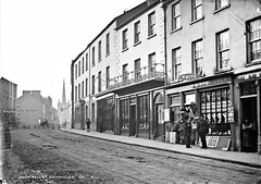 Fridays child is loving and giving! (National Library of Ireland on The Commons) Tags: robertfrench williamlawrence lawrencecollection lawrencephotographicstudio thelawrencephotographcollection glassnegative nationallibraryofireland townhallstreet enniskillen cofermanagh policeman posters cart shops churchspire boys ulster