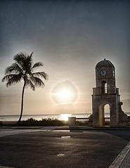 Between a Palm and a Clock (Emoya78) Tags: ocean trees sea sky sun seascape beach architecture clouds landscape island florida westpalmbeach palm clocktower palmtree palmbeach intracoastal