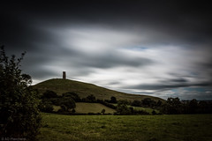 Under the sky of Avalon (Anthony Plancherel) Tags: category england glastonbury glastonburytor landscape places somerset travel longexposure sky cloud cloudy cloudysky greyclouds land landscapephotography travelphotography hill grass field bush tree hedgerow hedge tor tower church ruin stmichaels greatbritain british britain english unitedkingdom uk canon canon70d canon1585mm slope steep stone mythical avalon isleofglass wow