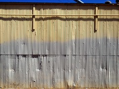 Unibrow (misterbigidea) Tags: city shadow urban abstract lines yellow wall fence silver landscape industrial pattern steel pipe rusty line faded eyebrow stockton corrugated unibrow fragment iseefaces facesinplaces sidesmirk