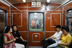 Subway commuters under watchful eyes (Lil [Kristen Elsby]) Tags: travel train underground subway asia metro korea retro passengers kimjongil editorial traincar passenger dailylife topv3333 northkorea pyongyang eastasia subwaycar dprk traincarriage travelphotography documentaryphotography kimilsung democraticpeoplesrepublicofkorea chosnminjujuiinminkonghwaguk pyongyangmetro dprofkorea canon5dmarkii lifeinnorthkorea