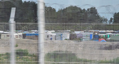 Behind the wire (Vee living life to the full) Tags: leger travel touring holiday nikond300 calais behindthewirecamp refugees makeshift tents caravans border control chaos checks drivers driving lorry bush home people controllee