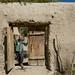 Michelle no portão de uma casa afegã